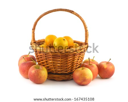 Many orange tangerines in brown wicker basket and some apples near isolated on white closeup - stock photo