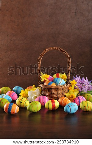many painted easter eggs with easter basket and hyacinth in front of brown background  - stock photo