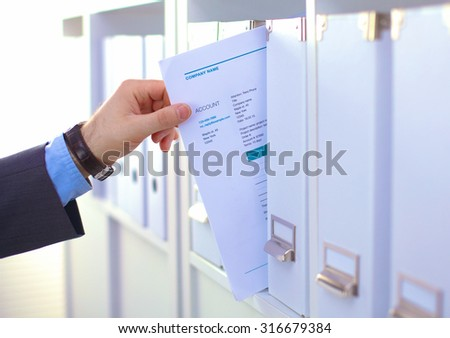 Many papers orderly arranged in a file shelves. And some are still on the table - stock photo