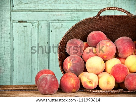 Many peaches spilling out of a basket - stock photo