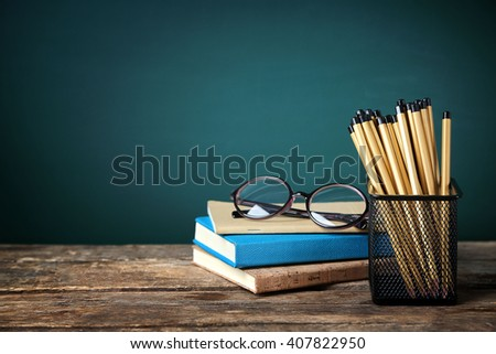 Many pencils in the metal holder on wooden table on green board background - stock photo