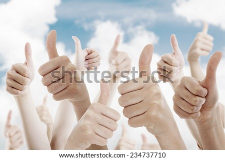 Many people holding their thumbs up on the sky - stock photo