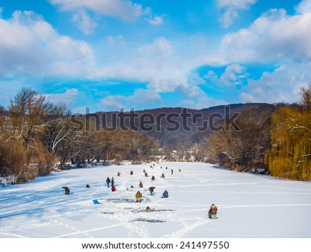 Many people ice fishing on a frozen river in winter sunny day - stock photo