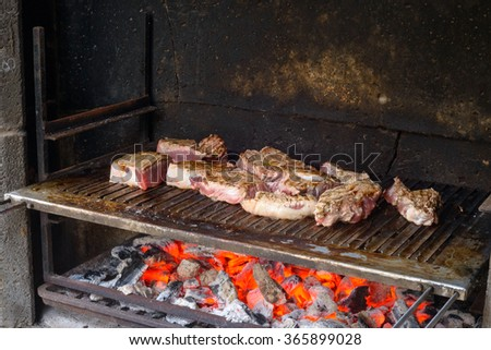 Many piece of beef meat grilling on a barbecue
