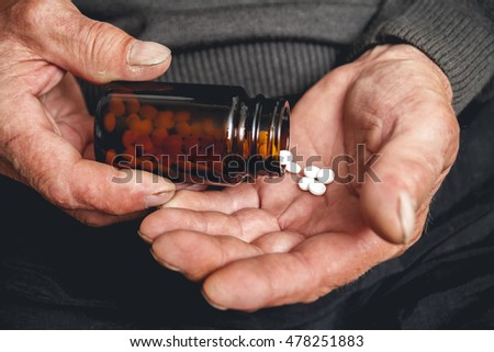 Many pills from a glass bottle in the Senior hands. Painful old age. Caring for the health of the elderly