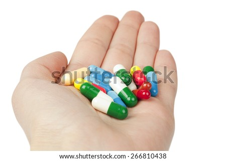 Many pills in the hand isolated on white. Medicine concept