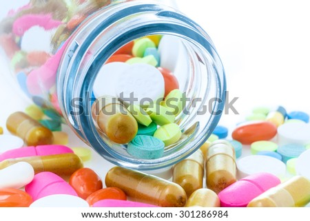 Many pills tablets and medicine capsules spilling out of a bottle - stock photo