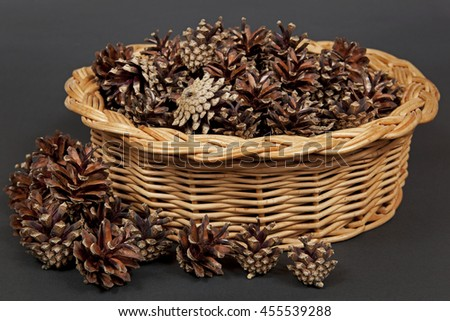 Many pine cones lying in the basket.