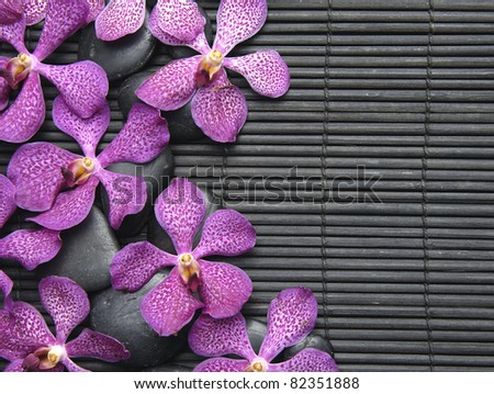 Many pink orchid laying on pebbles on bamboo stick straw mat - stock photo
