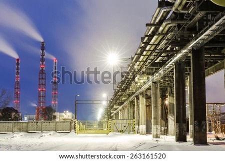 many pipes and smokestacks with industrial tower of metal on the chemical industry at night - stock photo
