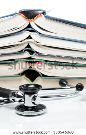 Many pitched books are placed in a stack and a stethoscope - stock photo