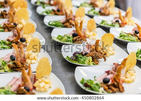 Many plates of appetizers being prepared in commercial kitchen - stock photo