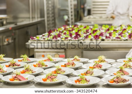 Many plates of carpaccio appetizers being prepared in commercial kitchen - stock photo