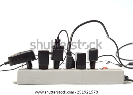 Many plugs and adapters plugged into electric power bar - stock photo