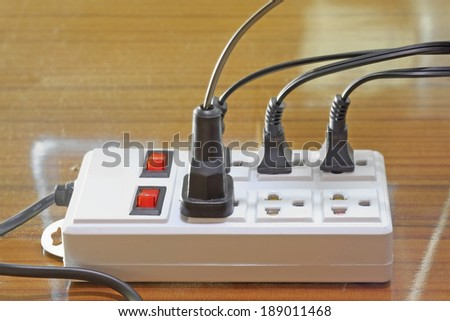 Many plugs plugged into electric power bar. - stock photo