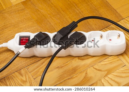Many plugs plugged into electric power bar on floor - stock photo