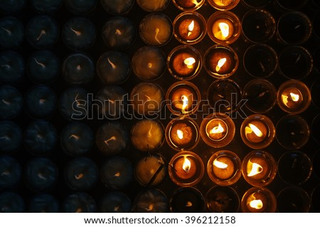 Many praying candle flames glowing in the dark, creating a spiritual atmosphere - stock photo