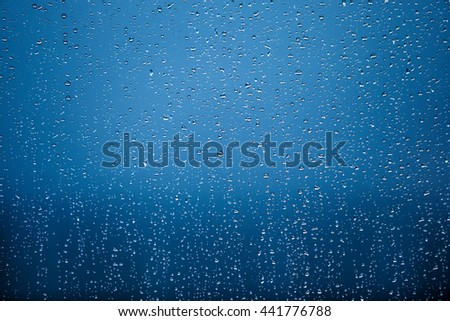 many raindrops on a transparent window blue