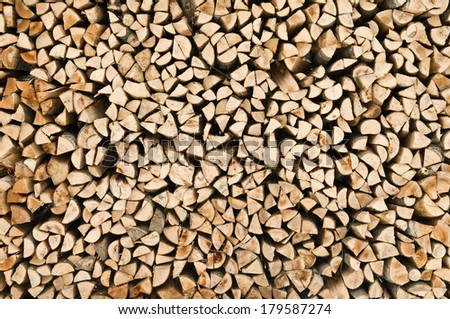 many raw firewood logs stacked texture background - stock photo