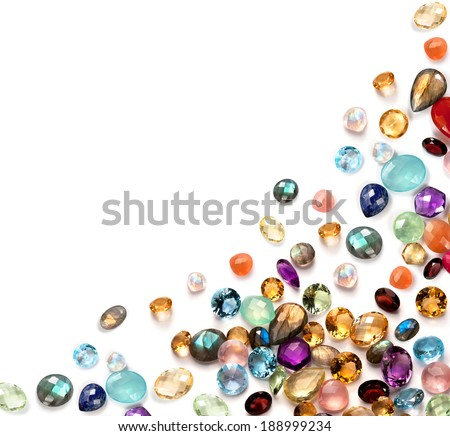 Many real colorful polished gemstones on the white background. Composition with empty space in the left top corner. - stock photo