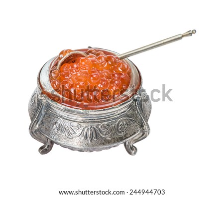 Many red caviar in a silver bowl with a silver spoon closeup