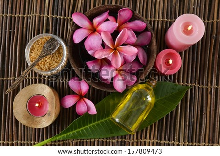 Many red frangipani in bowl ,red candle ,leaf ,salt in bowl on bamboo mat