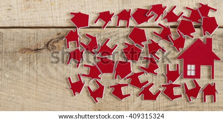 Many red house symbol on wooden background. Real-estate concept - stock photo