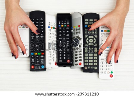 Many remote control devices in hands - stock photo
