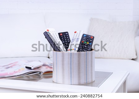 Many remote control devices on table in room - stock photo