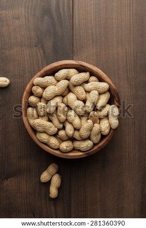 many roasted peanuts in wooden bowl on the table background - stock photo