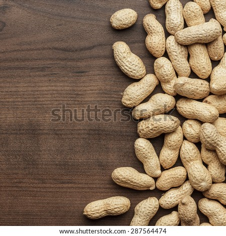 many roasted peanuts on the wooden table background - stock photo