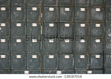 Many rows of old fashioned mailboxes that are weathered and worn - stock photo