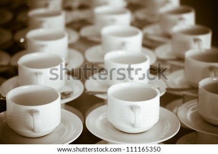 Many rows of pure white cup and saucer designed in vintage retro style. Note: the image contains grain as an element of style. - stock photo