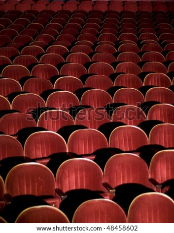 Many rows of red auditorium chairs