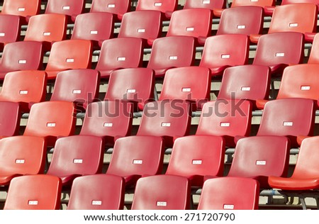 many rows of red chairs in a sports stadium on a hot summers day - stock photo