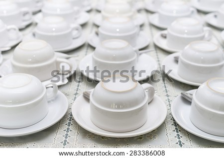 Many rows of white coffee cup with saucer and teaspoon on table - stock photo
