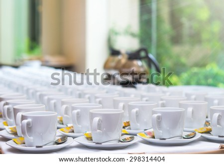 Many rows of white coffee cup with saucer and teaspoon on table and coffee maker background - stock photo