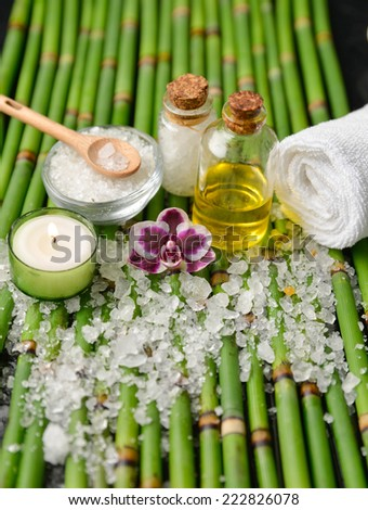 many salt with ,oil, towel, orchid salt in bowl, soap on bamboo grove - stock photo
