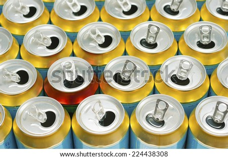 many same and one different opened beer can - stock photo