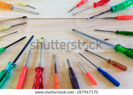 Many screwdrivers on wooden background - stock photo