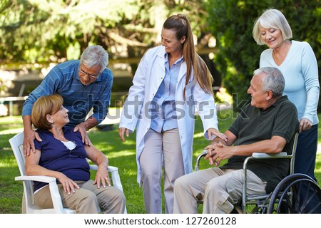 Many seniors relaxing in a park of a nursing home with geriatric nurse - stock photo