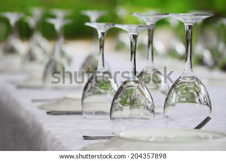 Many served wine glasses on the table turned upside-down - stock photo