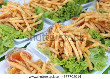 Many set of ready to serve french fries, decorated with green vegetable.  - stock photo