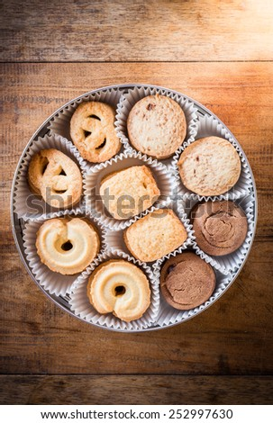Many shapes cookie in the box on wooden table. The view from the top - stock photo