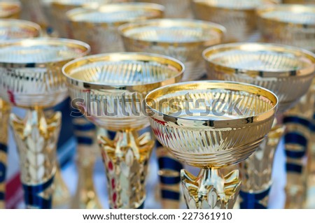 Many shiny gold trophies in a rows - stock photo