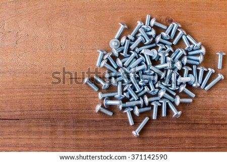 many silver screws on wood , Background  - stock photo