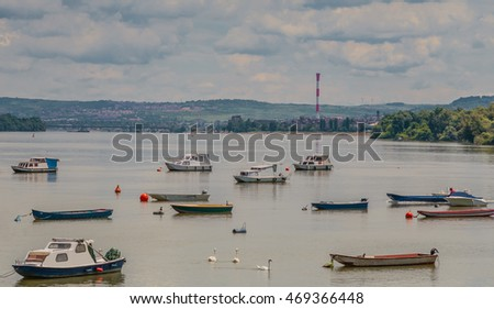 Many small fishing boats anchored on Danube river with beautiful blue sky. View from Zemun part of Belgrade, Serbia.