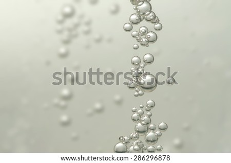Many small fizz bubbles floating in champagne - stock photo