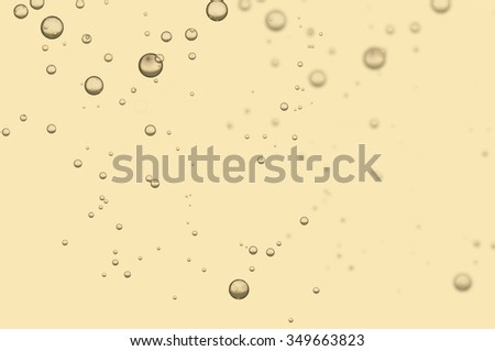 Many small golden fizz bubbles isolated over a light background