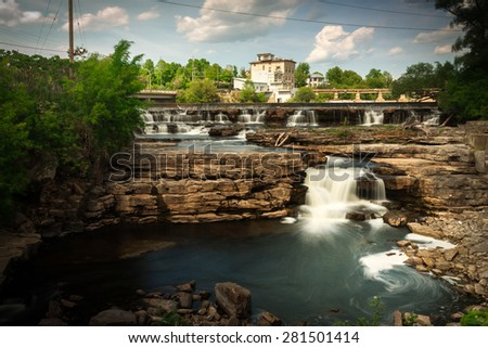 Many small waterfalls cascade over rocks in into a small pool in the heart of Almonte, Ontario Canada. Captured in a timed exposure. - stock photo